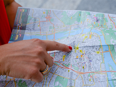 image of a finger pointing to a spot on a map